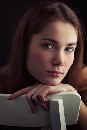 mujer pensativa: Mujer joven hermosa pensativa sentado en la silla a la luz cálida close-up Foto de archivo