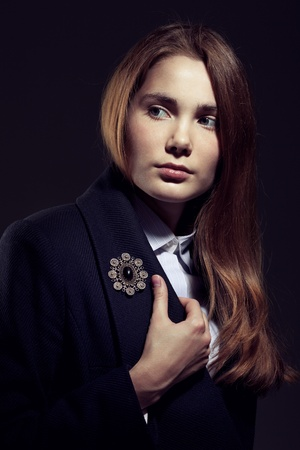 Irresistible young woman wearing a blue topcoat with a brooch on black background Stock Photo