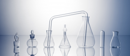 Empty laboratory glassware on bright blue background photo