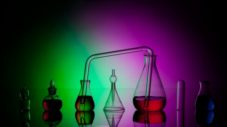 Laboratory glassware with liquids on dark colorful background photo