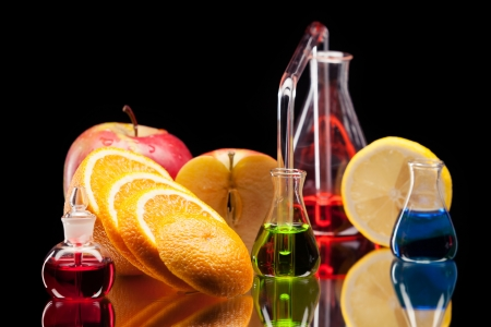 Still life of laboratory glassware with colorful liquids and fruits on black background Stock Photo