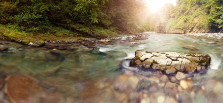 Panoramic view of Sochi river in mountains nearer to the river head, lens flares photo