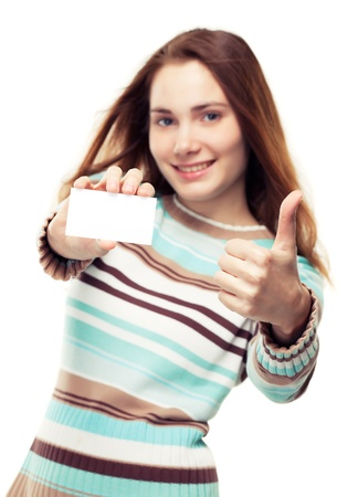 Beautiful young woman in a striped sweater showing a blank business card and thumb up, isolated on white, focus on hands Stock Photo - 14994999