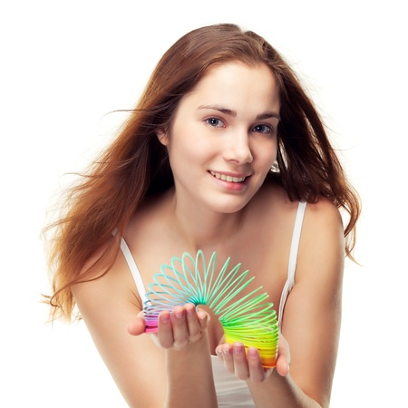 slinky: Beautiful girl playing with a colorful slinky. Can be concept of game, balance in diet etc, isolated on white