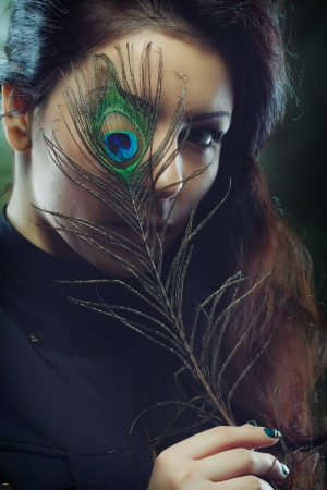 Young beautiful woman with long curly hair holding peacock feather in front of her face, dark green background photo