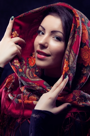 Beautiful young russian woman wearing red traditional russian shawl on black background photo
