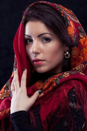 Beautiful young russian woman wearing red traditional russian shawl on black background Фото со стока