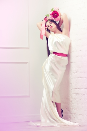 Beautiful young woman / bride in white silk long dress holding bouquet of peonies and roses lean against the wall Standard-Bild