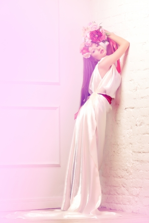 Beautiful young woman / bride in white long dress holding bouquet of peonies and roses lean against the wall