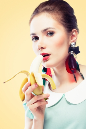 Young beautiful woman with red glamour lips and eye arrow make-up wearing fancy plastic earrings eating banana, on yellow background, pin-up style