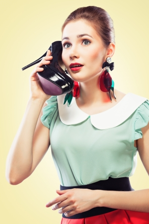 Excited pin-up girl using a shoe like a telephone holding it near her face and talking, yellow background  Stock Photo - 14996674