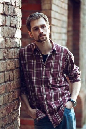Young handsome man leaning against the brick wall, he is wearing checked shirt and jeans  photo