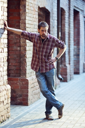Young handsome man leaning against the brick wall, he is wearing checked shirt and jeans