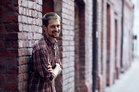 Smiling young man leaning against the brick wall, he is wearing checked shirt and jeans