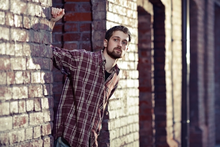 Young handsome man leaned against the brick wall and looking for someone, he is wearing checked shirt and jeans  photo