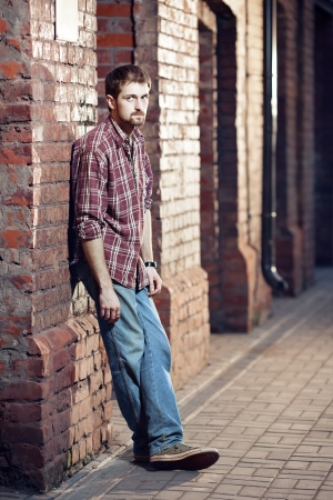 Young handsome man wearing checked shirt and jeans leaned against the brick wall waiting for someone photo