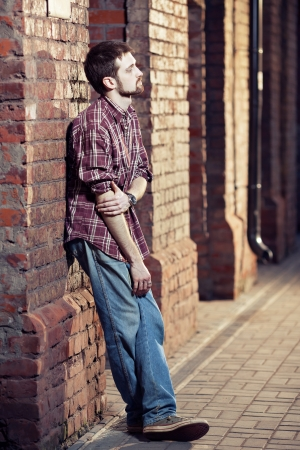 Pensive young man leaned against the brick wall and waiting for someone, he is wearing checked shirt and jeans
