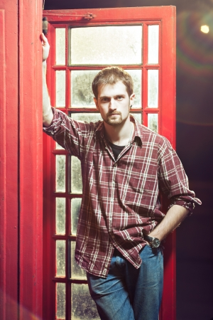 Young handsome man leaned against the red telephone booth, he is wearing checked shirt and jeans, dark background, lens flares photo