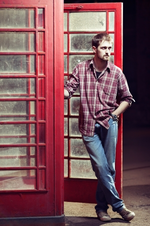 Young handsome man leaned against the red telephone booth, he is wearing checked shirt and jeans, dark background