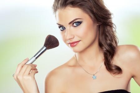 Young beautiful woman using a make-up brush, bright natural background  photo