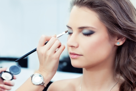 Make-up artist applying bright base color eyeshadow on model s eye and holding a shell with eyeshadow on background Stock Photo