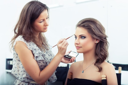 Make-up artist holding eyeshadows palette and applying eyebrow make-up, selective focus on model