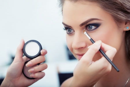 Make-up artist applying white eyeshadow in the corner of model s eye and holding a shell with eyeshadow on background, close up photo