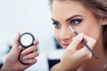 Make-up artist toepassing van witte oogschaduw in de hoek van het oog model s en het houden van een shell met oogschaduw op de achtergrond, close-up Stockfoto - 17413526