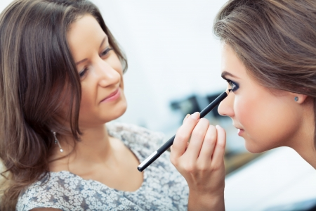 Make-up artist applying eyeliner on model s lower lid, selective focus on model, close up photo