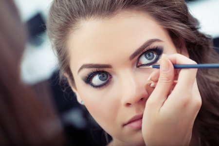 Make-up artist applying liquid eyeliner with brush, close up photo