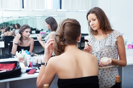 Make-up artist and model at work in front of mirror, selective focus on MUA looking at model