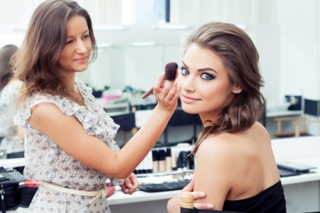Make-up artist applying powder with a brush on model s cheeks, selective focus on model looking at camera