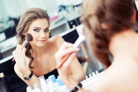 Reflection of young beautiful woman applying her make-up, looking in a mirror photo