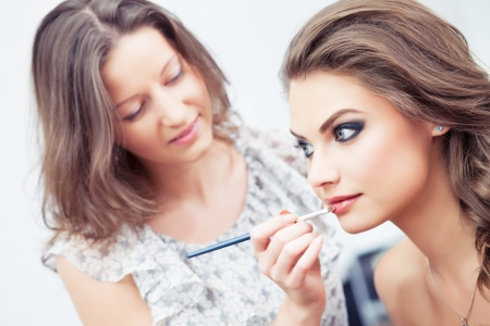 Make-up artist applying lipstick with a brush on model s lips, close-up