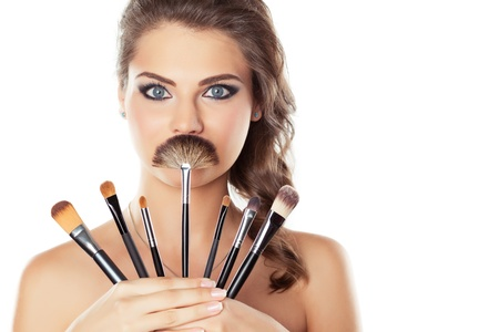 Beautiful young woman holding different make-up brushes, one of them is like mustache, isolated on white Stock Photo