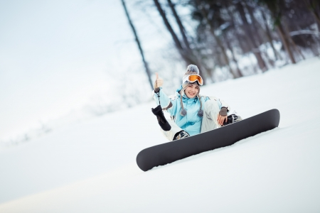 Young female snowboarder sitting on slope and showing thumb up, copy space photo