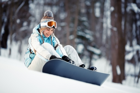 Young beautiful woman strapping on her snowboard at slope