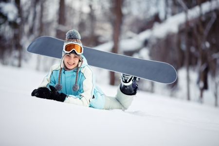 Young beautiful female snowboarder resting on ski slope, she is lying on stomach and smiling