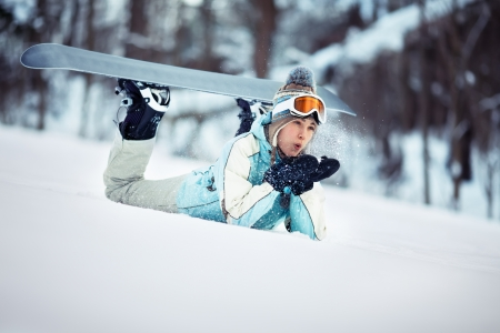 Young beautiful female snowboarder resting on ski slope, she is lying on front and blowing snow off her hands photo