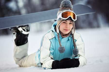 Young beautiful female snowboarder resting on ski slope, she is lying on front and smiling, close up photo