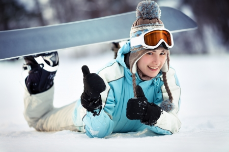 Young beautiful female snowboarder resting on ski slope, she is lying on front, showing thumbs up and smiling, close up photo