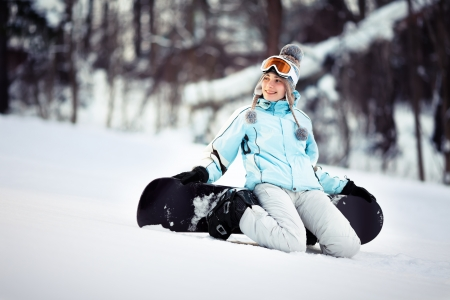 Young beautiful female snowboarder resting on ski slope, she is kneeling and smiling while looking away, copy space photo