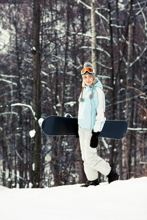 ski walking: Young pretty woman holding her snowboard and walking on ski slope in sunlight, wood on background, side view, copy space
