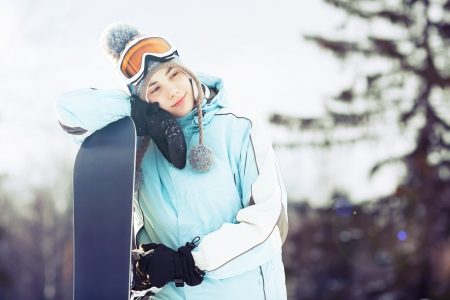 ski mask: Young woman leaning on her snowboard, she is looking away and smiling; copy space, close up, lens flare