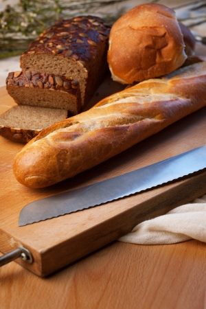 farinaceous: Brown bread, baguette and buns on bred-board