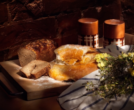 farinaceous: Still life with fresh-backed round loaf, brown bread and clay cups with milk, simple rural meal; light painting Stock Photo