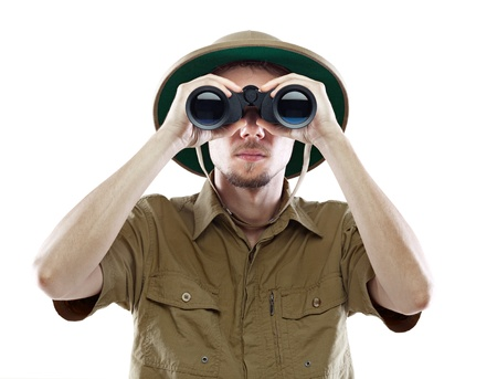 Young man in pith helmet looking through binoculars, isolated on white Standard-Bild