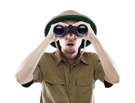 m�dula: Hombre joven que llevaba un casco de m�dula mirando a trav�s de un par de binoculares con una expresi�n de sorpresa, aislado en blanco Foto de archivo
