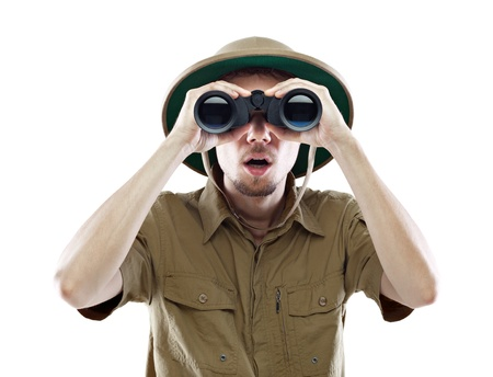 Young man wearing a pith helmet looking through a pair of binoculars with a surprised expression, isolated on white