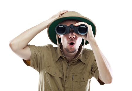 watcher: Young man wearing safari shirt and pith helmet looking through binoculars with a surprised expression, isolated on white